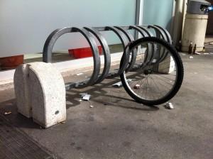 Ruota di bicicletta allucchettata al suo posto, orfana di tutta la bici mancante